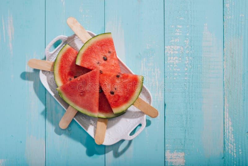 Plakken van watermeloen op plaat op blauw houten bureau royalty-vrije stock afbeelding