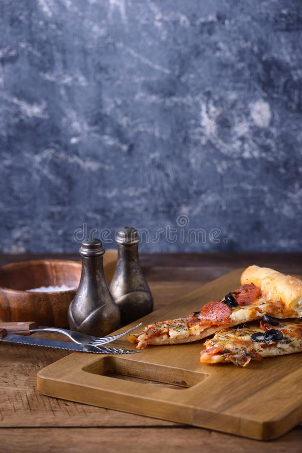 Plakkenpizza op houten raad stock afbeelding