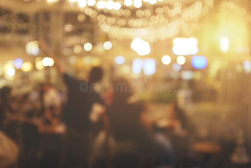 Plam ludzie w restauraci abstrakcjonistyczny bokeh w nocy przyjęciu dla tła obrazy stock