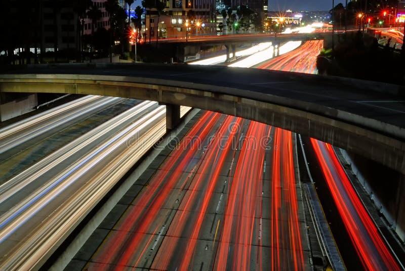 Plama światła ruchu przy półmrokiem i mosty krzyżuje nad 110 autostradą obraz stock