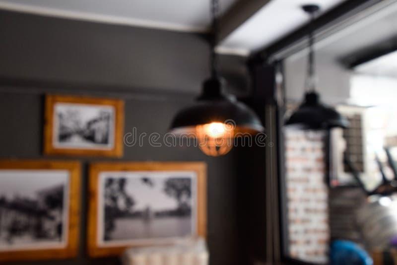 Plama wizerunek Zamazany - Defocus z ostrości czerni lampy na lub podsufitowym, siedzącym kącie w restauracji podczas dnia, - zdjęcie stock