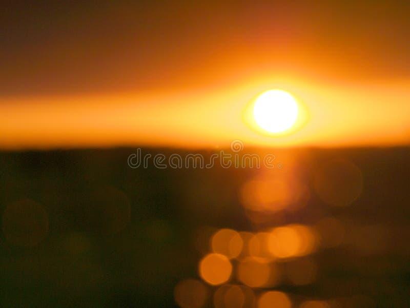 Plama zmierzch nad jeziorem z bokeh słońca światłem zdjęcie royalty free