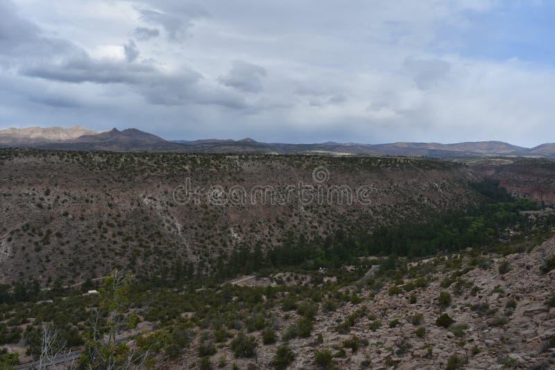 Planícies e montanhas com uma garganta e uns céus nebulosos fotos de stock