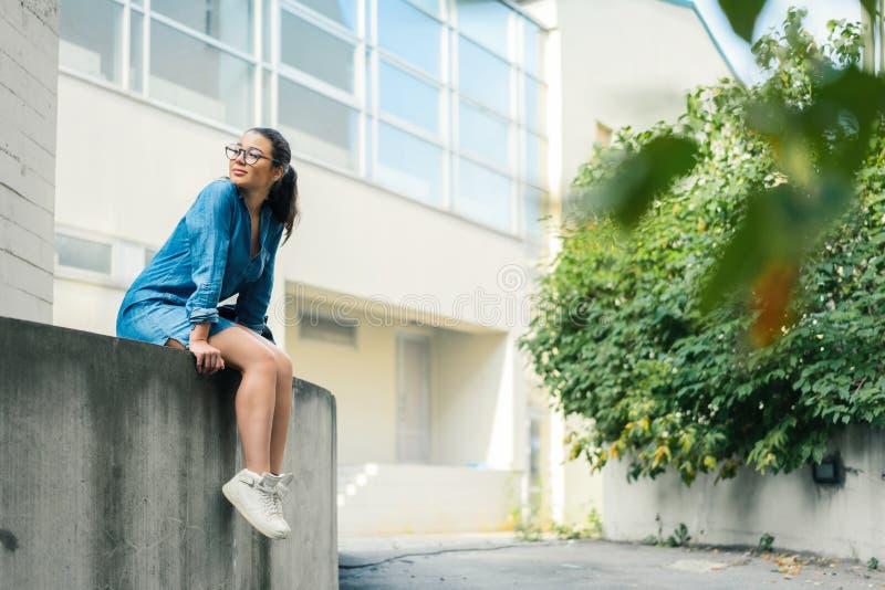 Plan éloigné de la jeune femme à lunettes attirante regardant de côté photo stock