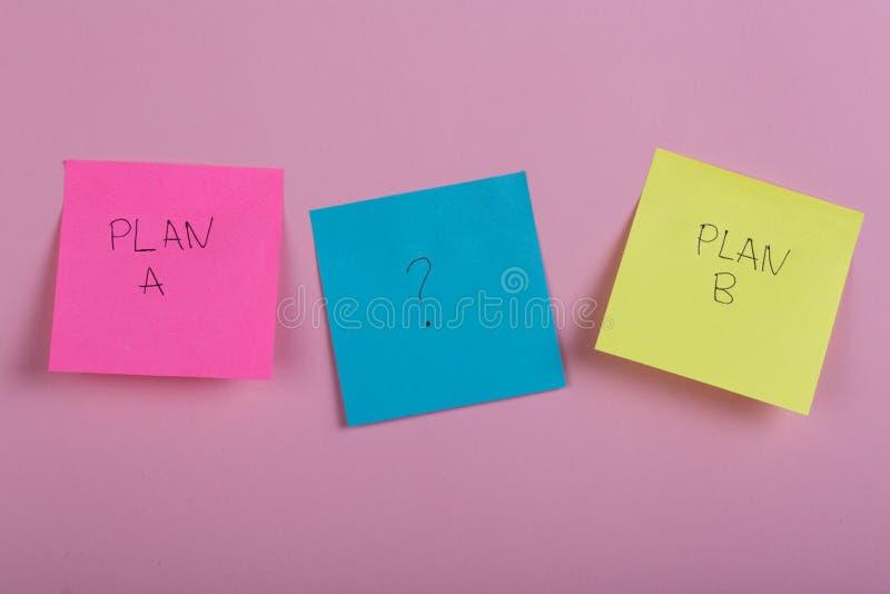 Plan bien escogido a del negocio o plan b en etiquetas engomadas coloridas de la oficina en fondo rosado imagen de archivo
