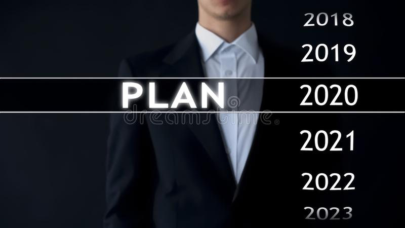 Plan for 2020, businessman chooses file on virtual screen, financial strategy. Stock photo stock photo