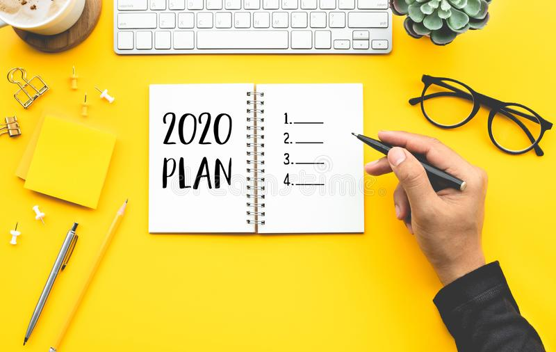 2020 pla2020 plan concepts with youngman writing checklist on notepad on color desk table. 2020 plan concepts with youngman writing checklist on notepad on color stock photography