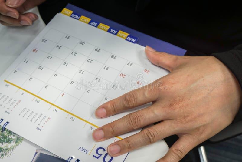 Plan d'homme d'affaires de foyer sélectif et marquer le calendrier de réunion en mai pour le rappel photos libres de droits