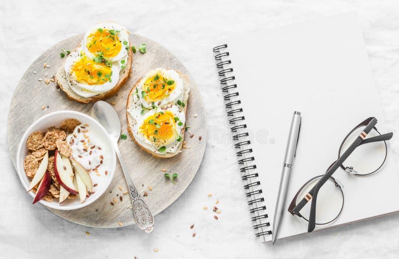 Plan de la dieta de la comida Desayuno o bocado sano - bocadillos con el queso suave y el huevo hervido, yogur griego con el cere imagenes de archivo