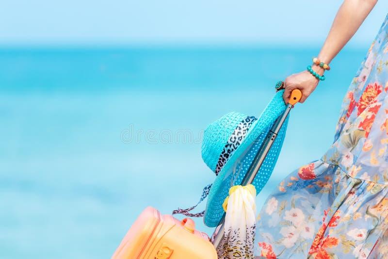 Plan de viaje Viajero de las mujeres de la mano que sostiene el equipaje anaranjado que camina en la playa Vacaciones de verano d foto de archivo libre de regalías