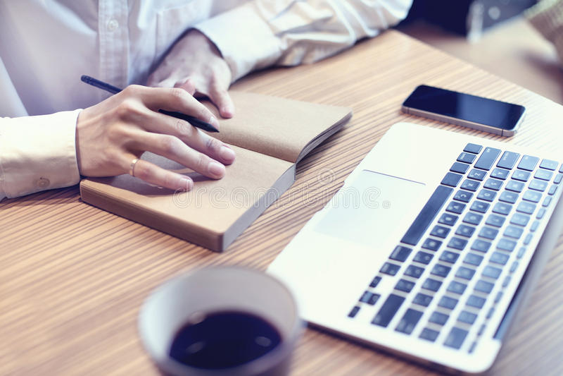 Plan empresarial de la escritura del hombre de negocios de la contabilidad, ordenador portátil del uso y teléfono móvil en el caf imagen de archivo