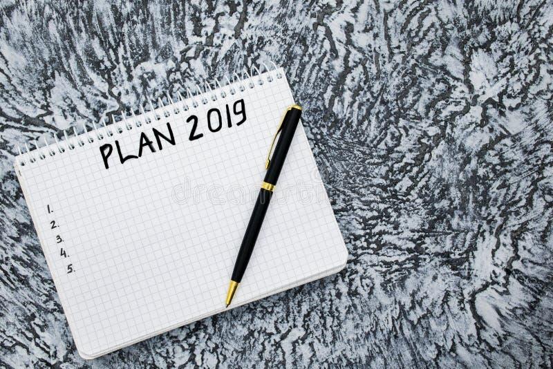 Plan för 2019, notepad och penna på en texturerad grå bakgrund fotografering för bildbyråer