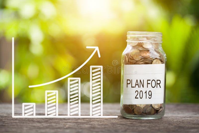 Plan för ord 2019 med myntet i exponeringsglaskrus och graf upp finansiellt begrepp royaltyfri bild