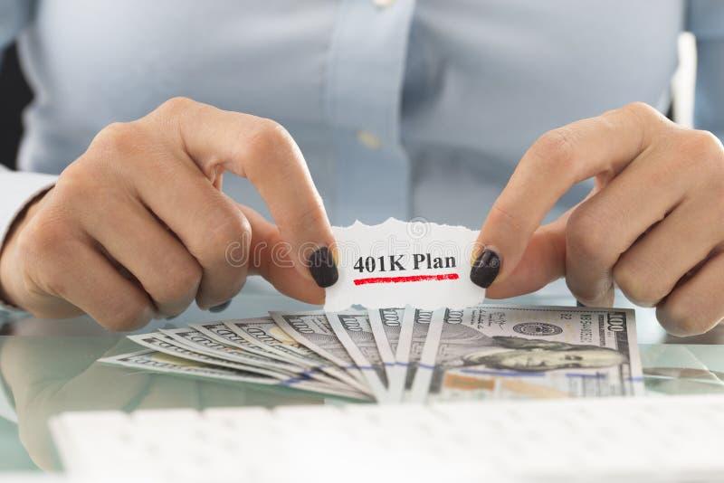 plan 401k för avgången med affärskvinnan och kassa oss dollar på tabellen arkivbild
