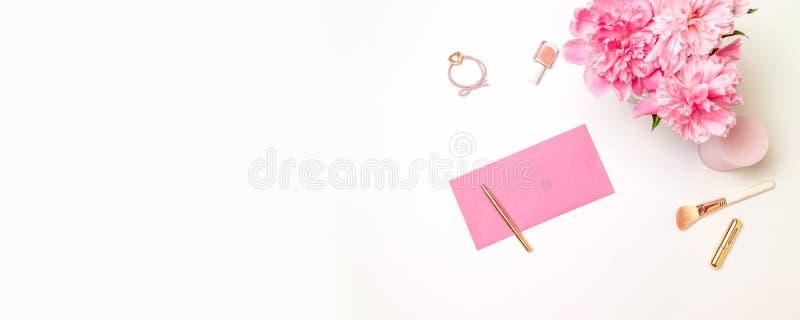 Plan lekmanna- bästa sikt av ett rosa pappers- kuvert med en guld- penna, kvinnors tillbehör, en bukett av rosa pioner, stearinlj arkivbilder