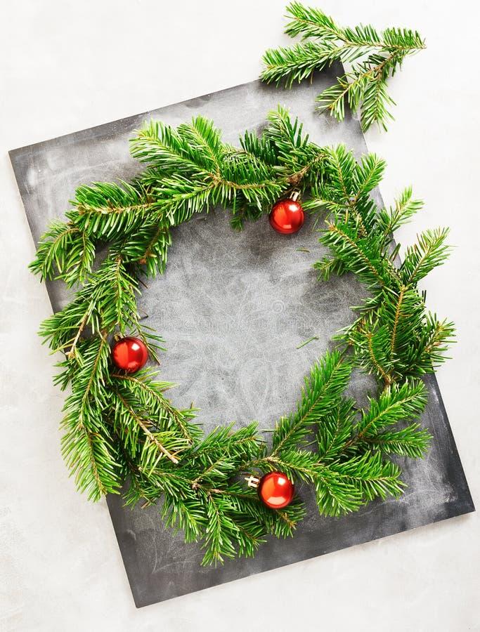 Plan lekmanna- gr?n julkrans f?r b?sta sikt p? den svart tavlan som t?ckas med vit krita Traditionellt garneringbegrepp f?r nytt  arkivfoto