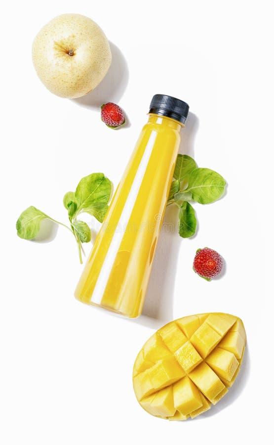 Plan lekmanna- gul flaska för bästa sikt av fruktsaft med spenat, jordgubbar mango och päronet på vit bakgrund Sund livsstil som  royaltyfri bild
