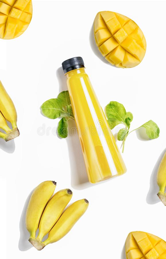 Plan lekmanna- gul flaska för bästa sikt av fruktsaft med spenat, mango och bananen på vit bakgrund Sund livsstil, vegetarisk mat royaltyfri bild