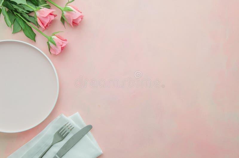 Plan lekmanna- hörnrestaurangtabell för romantisk matställe med rosa rosa blommor, maträtt- och bestickkniv, gaffel och servetter arkivfoto