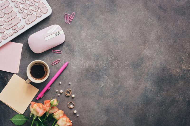 Plan lekmanna- kvinnaworkspace - modernt tangentbord, mus, kopp kaffe, rosa blommor, smycken och brevpapper på en mörk lantlig ba arkivbilder