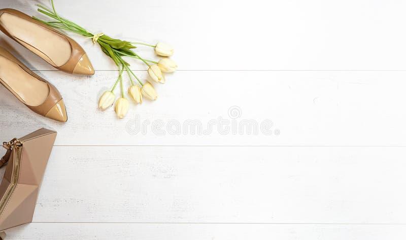 Plan lekmanna- kvinnlig dräktsamlingsklänning: tulpan för hjärta för beige skohandväskatillbehör guld- och leksakhund på vit träb arkivbild