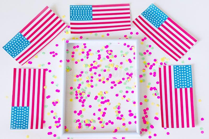 Plan lekmanna- sammansättning med amerikanska flaggan på en vit bakgrund Flaggor av USA och konfettierna på en vit bakgrund Lyckl fotografering för bildbyråer