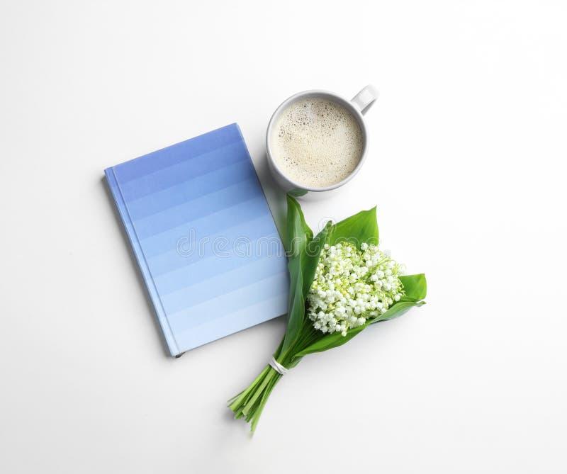 Plan lekmanna- sammansättning med anteckningsboken, liljekonvaljbuketten och kaffe royaltyfria bilder
