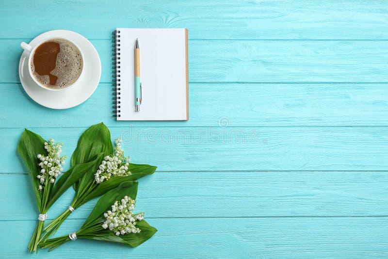 Plan lekmanna- sammansättning med anteckningsboken, liljekonvaljbuketter och kaffe på träbakgrund royaltyfria bilder