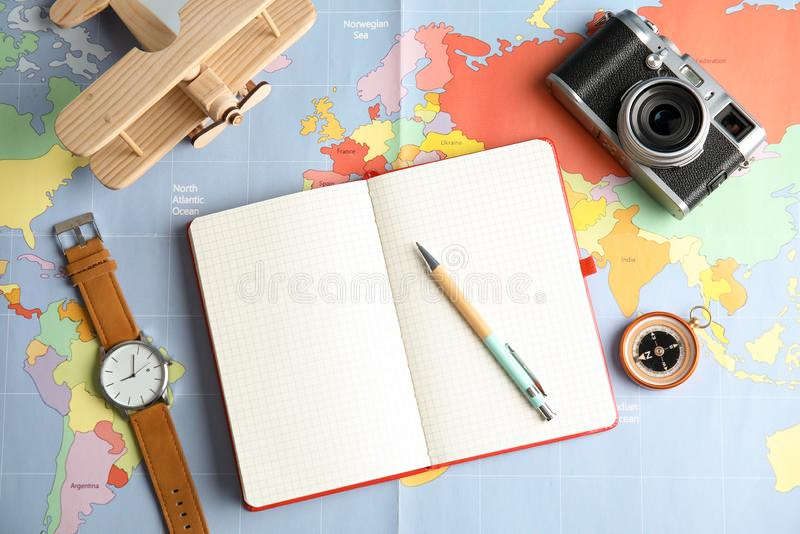 Plan lekmanna- sammansättning med anteckningsboken och kamera på världskartan, utrymme för text arkivfoton