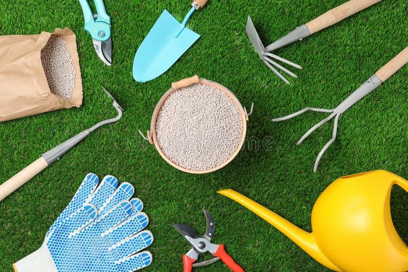 Plan lekmanna- sammansättning med att arbeta i trädgården hjälpmedel och kemisk gödningsmedel på gräsplan royaltyfri bild