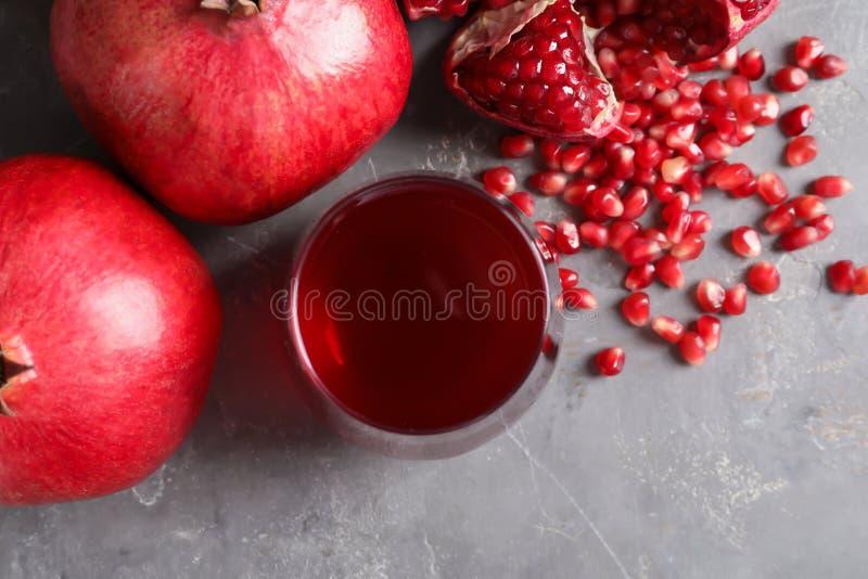 Plan lekmanna- sammansättning med exponeringsglas av nya granatäpplefruktsaft och frukter arkivbild