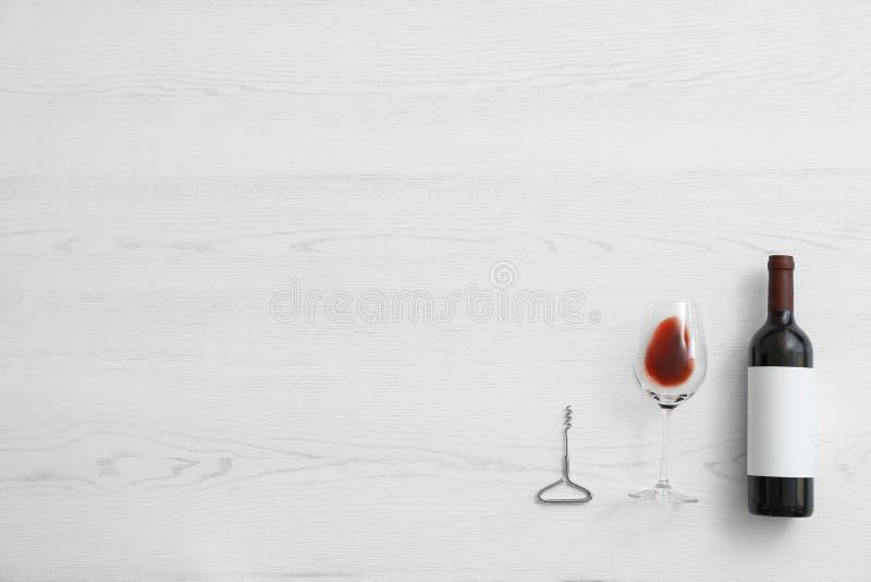 Plan lekmanna- sammansättning med flaskan av vin och elegant exponeringsglas på vit träbakgrund royaltyfria bilder