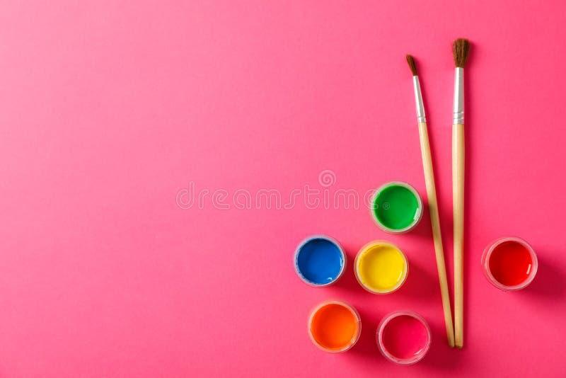 Plan lekmanna- sammansättning med gouache- och målarfärgborstar på rosa bakgrund arkivfoto