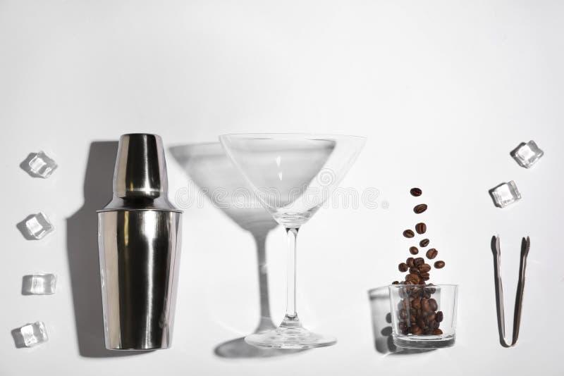 Plan lekmanna- sammansättning med kaffebönor, iskuber och stångutrustning Alkoholcoctailrecept - espresso arkivbilder