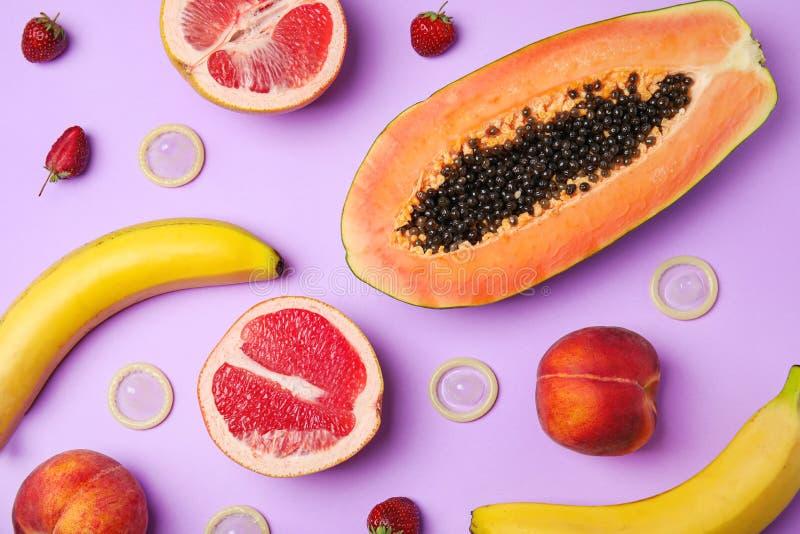 Plan lekmanna- sammansättning med kondomar och exotiska frukter på lila bakgrund erotiskt arkivbild