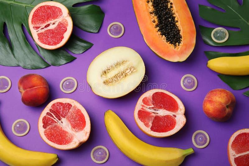 Plan lekmanna- sammansättning med kondomar och exotiska frukter på purpurfärgad bakgrund erotiskt fotografering för bildbyråer