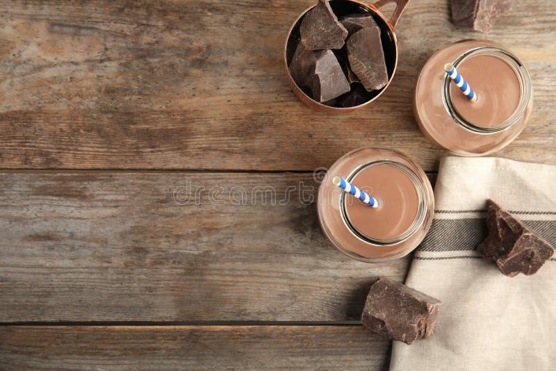 Plan lekmanna- sammansättning med krus av smaklig choklad mjölkar och gör mellanslag för text på träbakgrund fotografering för bildbyråer