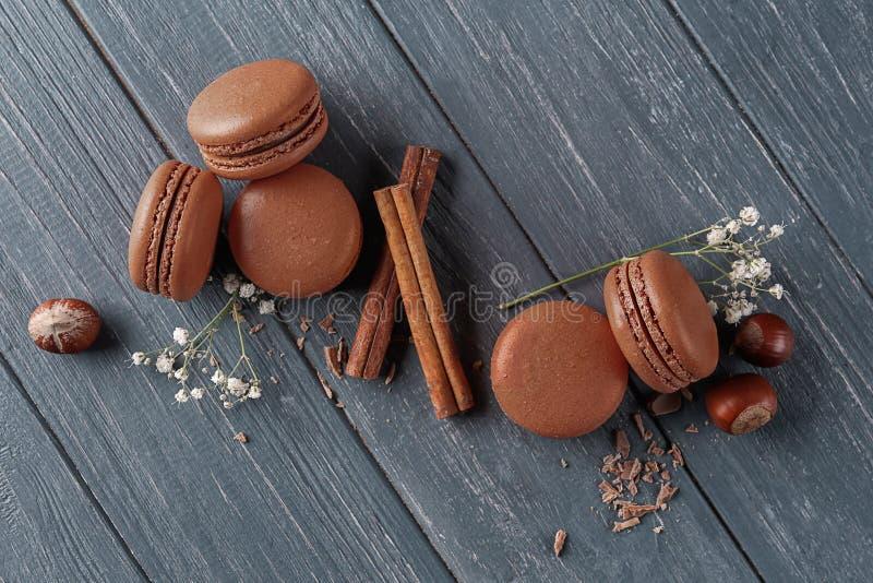 Plan lekmanna- sammansättning med läckra chokladmacarons och kanelpinnar på träbakgrund royaltyfria bilder