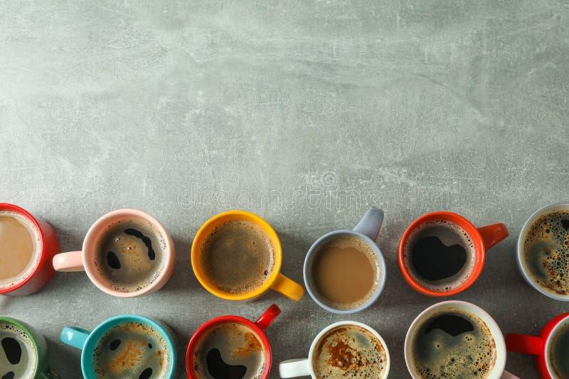 Plan lekmanna- sammansättning med mångfärgade koppar kaffe på grå bakgrund, bästa sikt arkivfoto