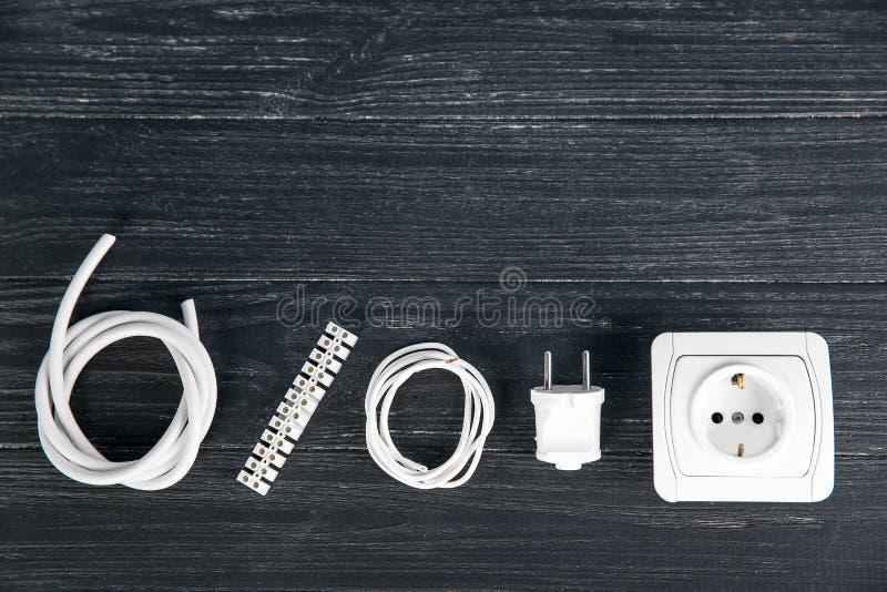 Plan lekmanna- sammansättning med makthåligheten, trådar, proppen och det elektriska kontaktdonet på träbakgrund arkivbilder