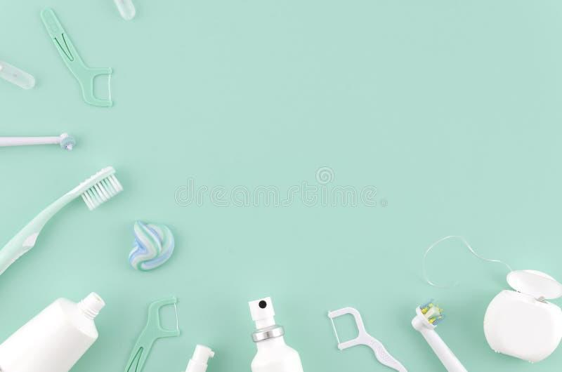 Plan lekmanna- sammansättning med manuella tandborstar och produkter för muntlig hygien på mintkaramellbakgrundsStomatologist åtl royaltyfri foto