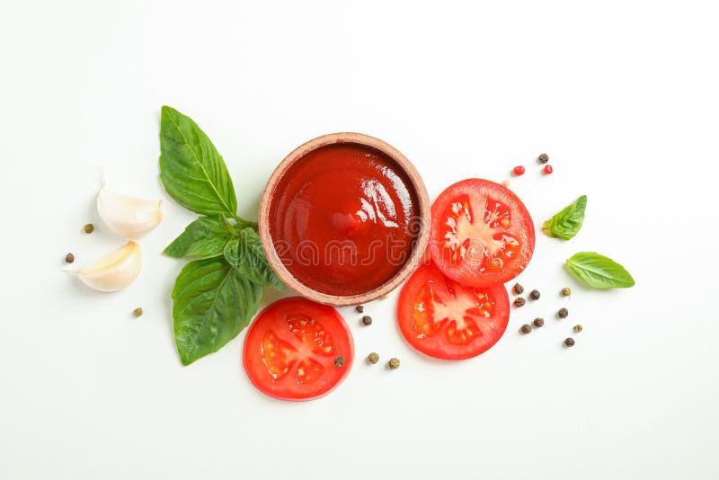 Plan lekmanna- sammansättning med nya skivor, basilika, peppar, vitlök och sås för körsbärsröda tomater på vit bakgrund, utrymme  royaltyfri foto