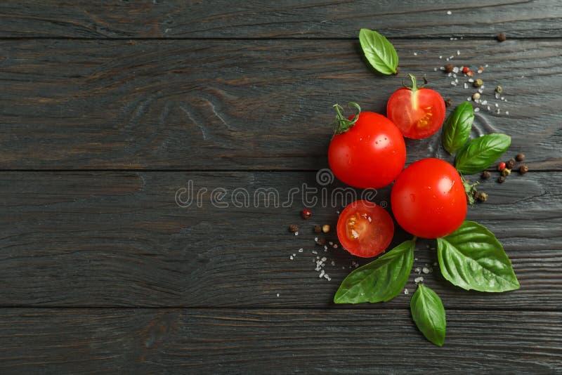 Plan lekmanna- sammansättning med nya tomater, saltar, peppar och basilika på träbakgrund, utrymme för text royaltyfri fotografi