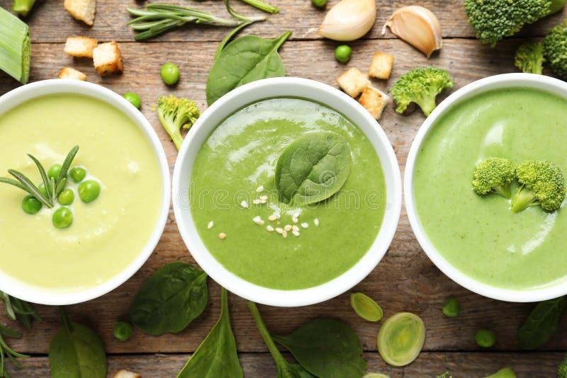 Plan lekmanna- sammansättning med olika detoxsoppor för ny grönsak som göras av gröna ärtor, broccoli och spenat i disk arkivfoton