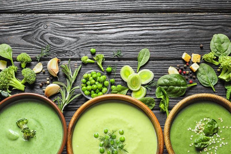 Plan lekmanna- sammansättning med olika detoxsoppor för ny grönsak som göras av gröna ärtor, broccoli och spenat i disk på tabell royaltyfri bild