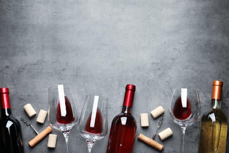 Plan lekmanna- sammansättning med olika viner på grå bakgrund royaltyfri foto