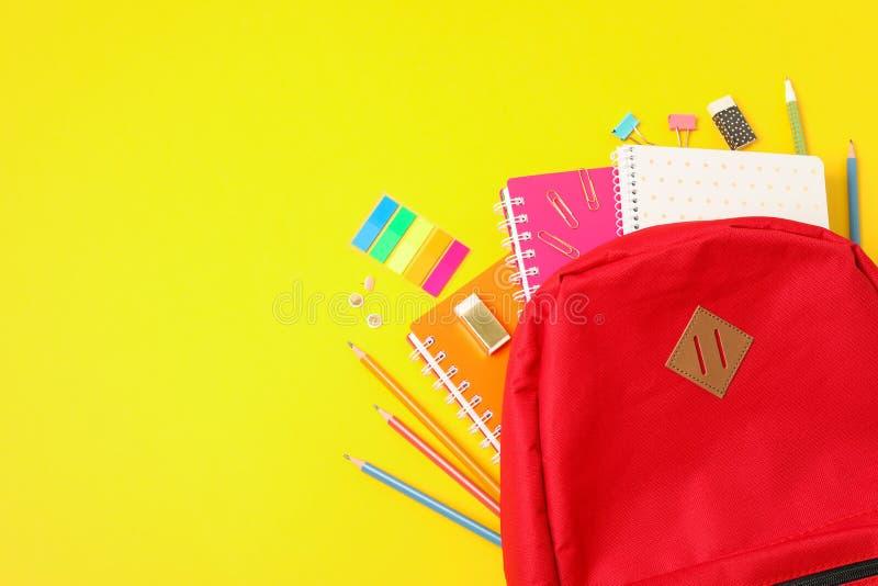 Plan lekmanna- sammansättning med ryggsäck- och skolatillförsel arkivfoton