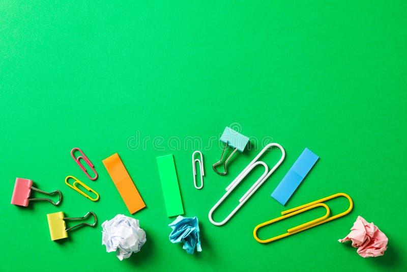 Plan lekmanna- sammansättning med skrynkliga pappers- bollar, gem och klistermärkear på färgbakgrund royaltyfri fotografi
