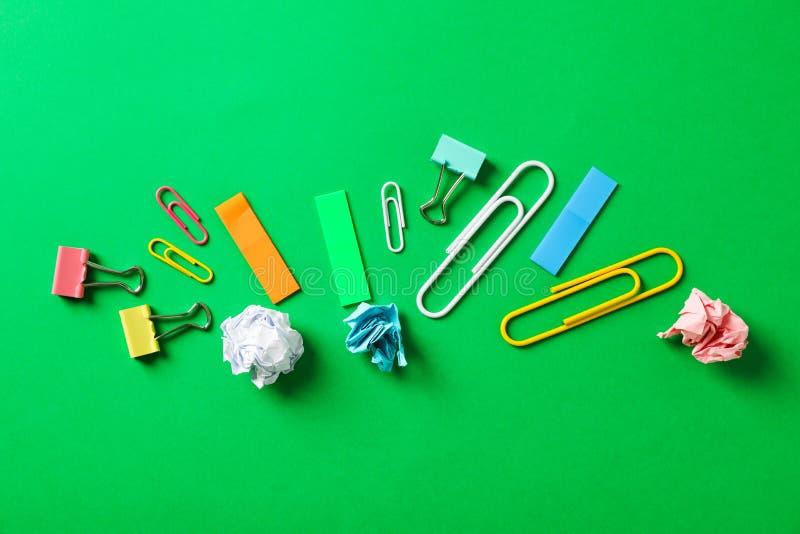 Plan lekmanna- sammansättning med skrynkliga pappers- bollar, gem och klistermärkear på färgbakgrund arkivbilder