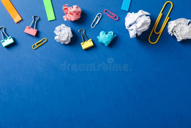 Plan lekmanna- sammansättning med skrynkliga pappers- bollar, gem och klistermärkear på färgbakgrund arkivbild